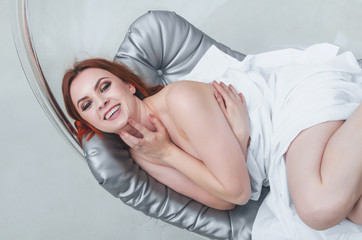 Beautiful nude woman lying on a gray mattress hanging seat, white cloth. Women's health. sexuality.