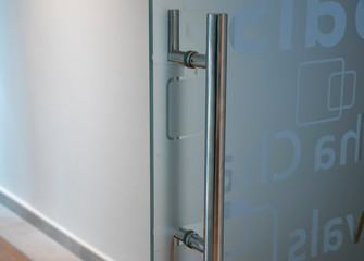 Glass door with metal handle and signs