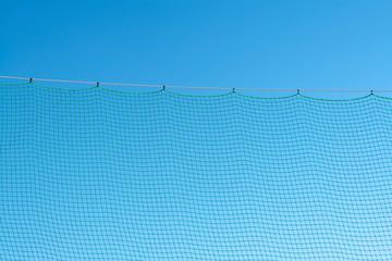 grünes Netz vor blauem himmel