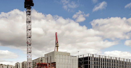 crane and concrete pump with tall arm in Apartments construction site