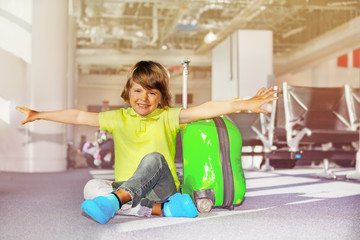 Boy sits with hands like wings at airport terminal