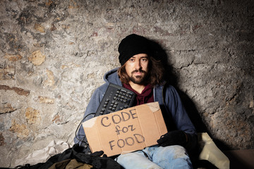 Man sits on floor with keyboard and cardboard sign
