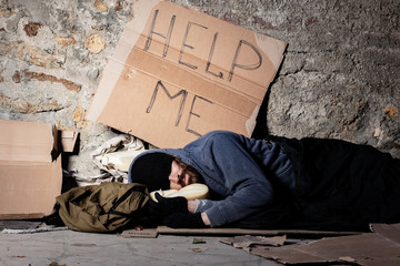 Beggar in tattered clothes sleeping at sidewalk
