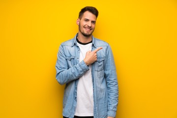 Handsome man over yellow wall pointing to the side to present a product Wall mural