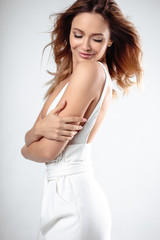 Fashion beauty portrait of young stylish woman in a white costume posing over white background isolated