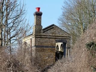 Disused and abandoned railway shed with red bucket on top of chimney, Chorleywood, Hertfordshire