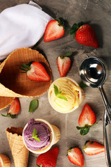 Set of ice cream scoops of different colors and flavours with berries, mint and fruits on table