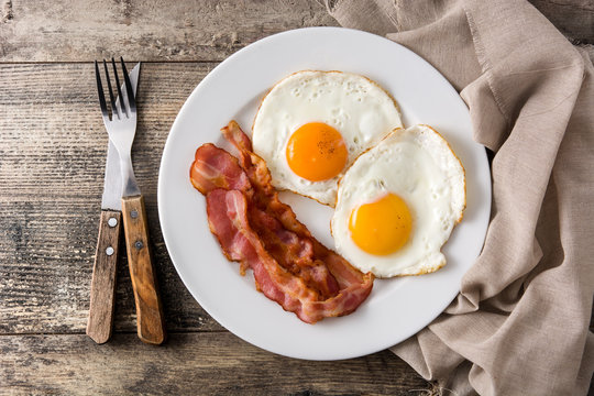 Fried eggs and bacon for breakfast on wooden table. Top view