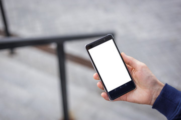 Cropped shot view of man's hands holding smart phone with blank copy space screen for your text message or information content, men reading text message on cell telephone during in urban location