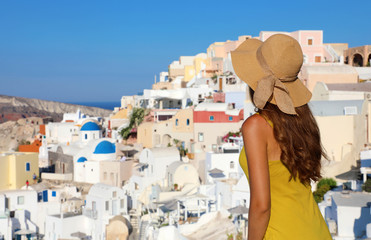 Young woman looks at Oia village in Santorini Island, Greece. The famous resort Greek Island is the main tourist attraction of Mediterranean. Back view of traveler girl visits Santorini.