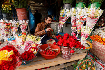 A man wraps red roses for sale ahead of Valentine's Day at a flower shop in Peshawar