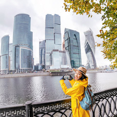 Young woman taking photo on her smartphone in business center skyscrapers in big city