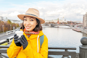 Happy asian traveler girl drinking hot coffee at the background of the Moscow River and Kremlin castle