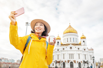 Happy asian tourist woman taking selfie at the Cathedral of Christ the Savior. Travel and tourism Landmark and destinations in Russia and Moscow concept.