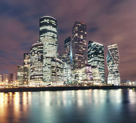 Illuminated Skyscrapers in Moscow City or international business centre at night time with lights, view from water pond embankment with reflections