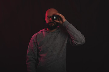 Photographer looking through photo lens in studio with vintage or retro lighting