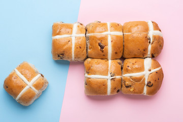 Six hot cross buns, traditional British Easter food on pink and blue background, top view, selective focus