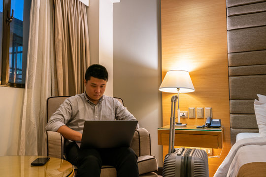 Young Asian businessman working late in hotel room