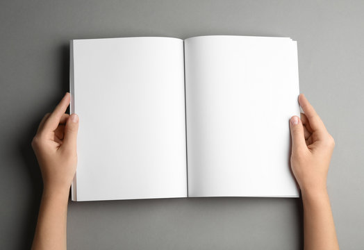 Woman holding brochure with blank pages on grey background, top view. Mock up for design