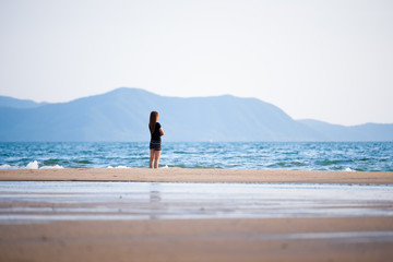 Business woman standing and relaxing on the beach at evening. To watch the beautiful sunset. How to live an adult woman's life on weekends or casual relaxation.