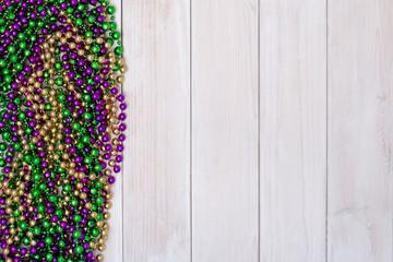 Mardi Gras beads on white wooden backgound
