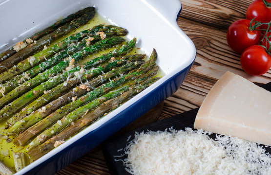 Green juicy asparagus is in ceramic form in olive oil