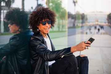 Young black man sitting with mobile and headphones in sunny city