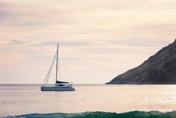 Yacht away sailing the sea in the sunset with the mountain background