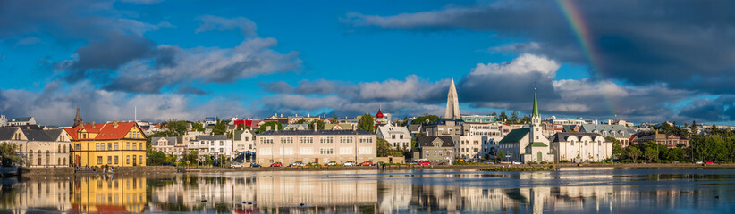 Panoramic view of Reykjavik downtown with lake on Iceland during sunset with rainbow, summer time