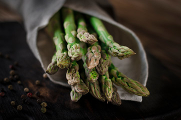 Green juicy asparagus is lying on a wooden board on a brown wooden table.