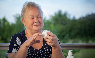 beautiful elderly woman doing make-up outdoors at home veranda