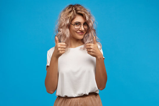Charming gorgeous young female hipster with voluminous pinkish hair smiling happily at camera, showing thumbs up gesture, being glad for you, saying: Good job. Happy woman showing approval sign