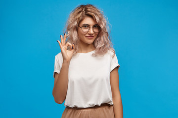 Positive friendly looking young woman with curly pinkish hair looking at camera with cute confident smile, making ok gesture. Pretty girl in round eyewear saying that everything is under control