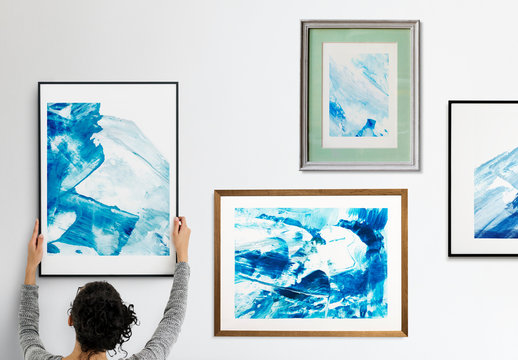 Person Hanging Four Art Frames on White Wall Mockup