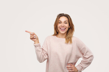 Cheerful female pointing aside and laughing
