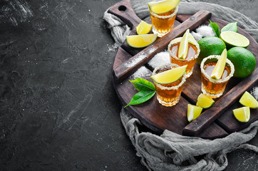 Gold tequila with lime and salt on black stone background. Top view. Free space for your text.