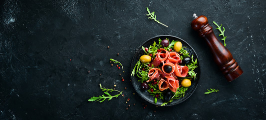 Salad with Prosciutto, olives and arugula. Cold snacks. Top view. Free space for your text.