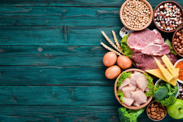 Fotomurales - Balanced diet food background. Protein foods On a blue wooden background. Free space for your text.
