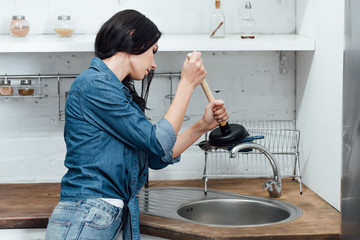 Concentrated woman in denim shirt using plunger in kitchen