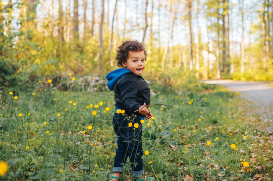 Adorable african toddler boy hiking in spring forest