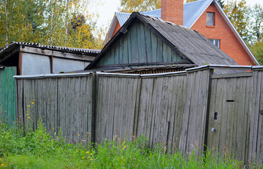 The old rickety fence and buildings on a country plot in the settlement