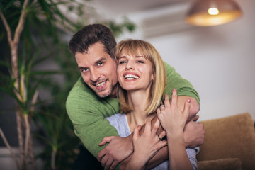 Loving young couple hugging and relaxing on sofa at home, selective focus.