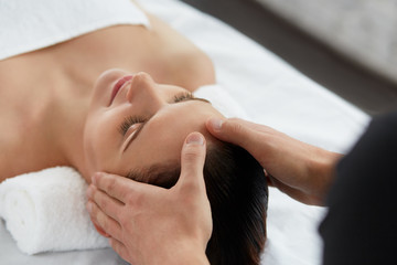 Young beautiful woman enjoying anti-aging facial massage.Male therapist making head massage to female client.Professional masseur.Relaxation,beauty,spa,body and face treatment concept.