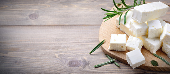 Feta cheese with rosemary on wood background. Top view with space for text