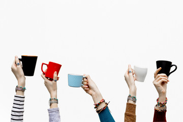 Many different hands holding coffee cups on isolated white background.