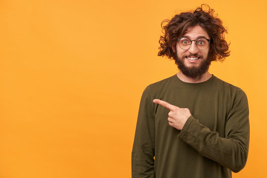 Closeup of a bearded young guy looks delighted gladden amazed pointing with index finger aside on blank copy space for your message or advertisement,smiles,on yellow background