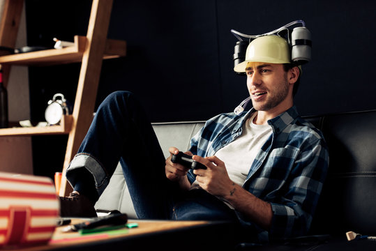 happy man in beer helmet playing video game at home