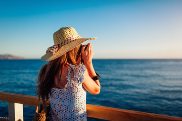 Young woman traveler taking photos of sea landscape on pier using camera. Summer fashion