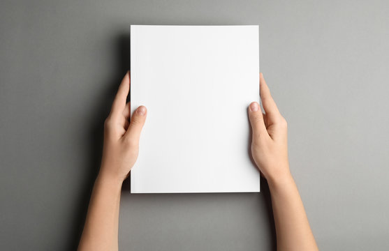 Woman holding brochure with blank cover on grey background, top view. Mock up for design