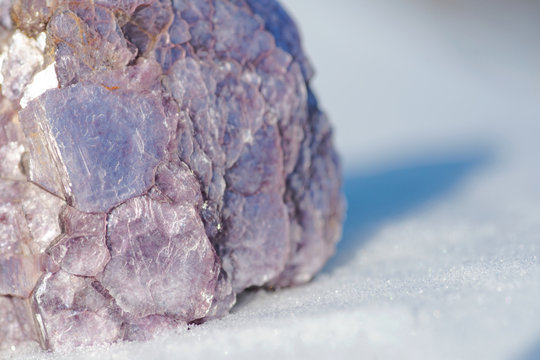 Rough Purple Lepidolite cluster from Brazil on white snow at a sunny winter day. Lepidolite Mica Slices.